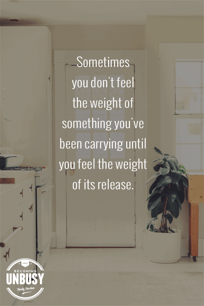 """A white door and bright entry way with the minimalism quote, """"Sometimes you don't feel the weight of something you've been carrying until you feel the weight of its release."""""""