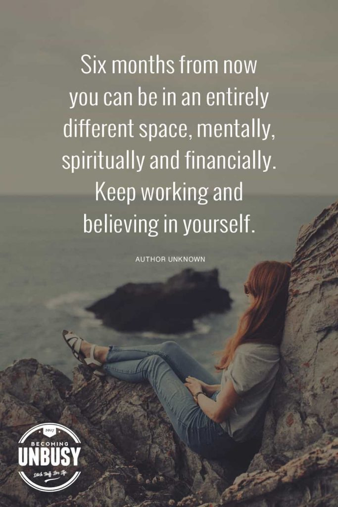 """A woman sitting on large rocks looking out at the ocean with a quote about how to start over written overtop reading, """"Six months from now you can be in an entirely different space. Keep working and believing in yourself."""""""