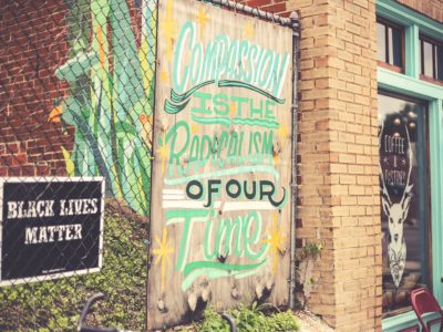"""Street art reading, """"Black lives matter. Compassion is the radicalism of our time."""""""
