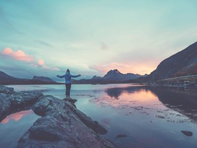 An adventerous woman standing on the edge of a rock with her arms up looking out at a lake and mountains at sunset.