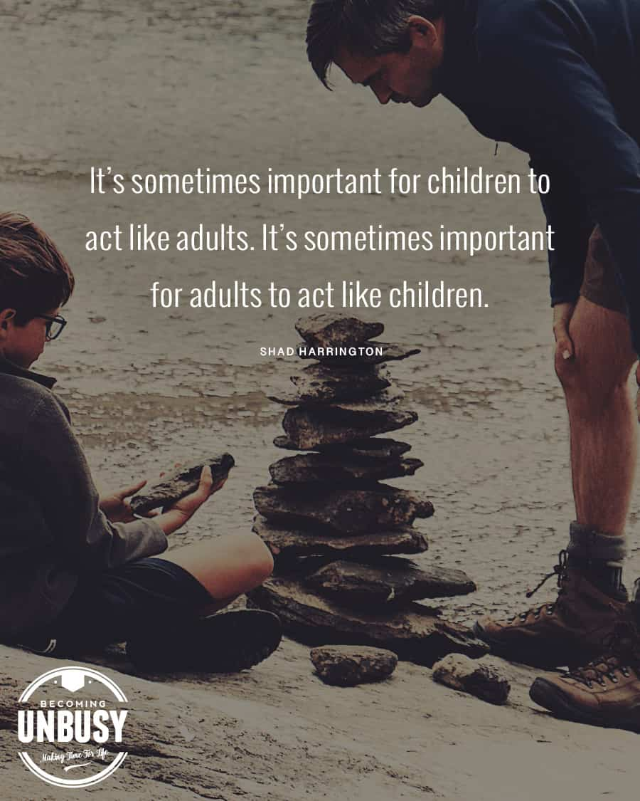 """Father and son stacking rocks on the beach with the following quote on top, """"It's sometimes important for children to act like adults. It's sometimes important for adults to act like children."""""""