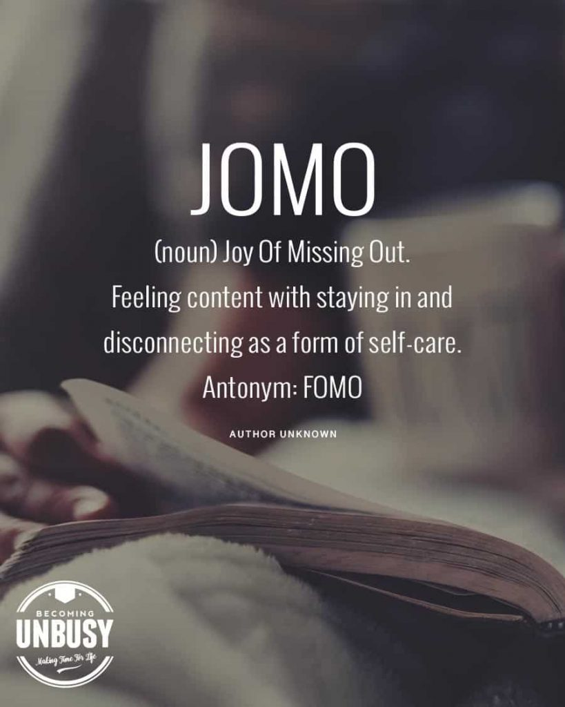 "A woman leading a simple life, flipping pages of a book with this text written overtop, ""JOMO (noun) Joy Of Missing Out: Feeling content with staying in and disconnecting as a form of self-care. Antonym: FOMO"""