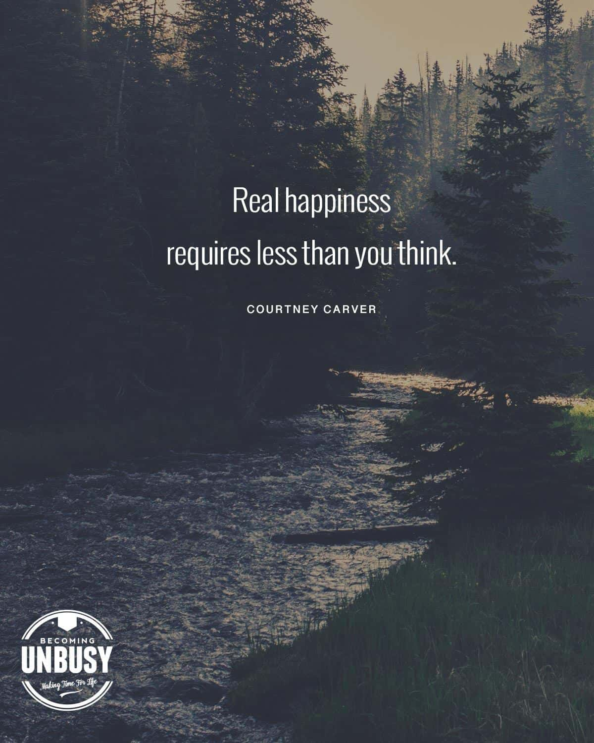 """A river in the forest with the following quote over top, """"Real happiness requires less than you think."""" by Courtney Carver."""