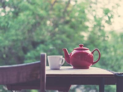 A tea pot and cup sitting on an outside table with a chair.