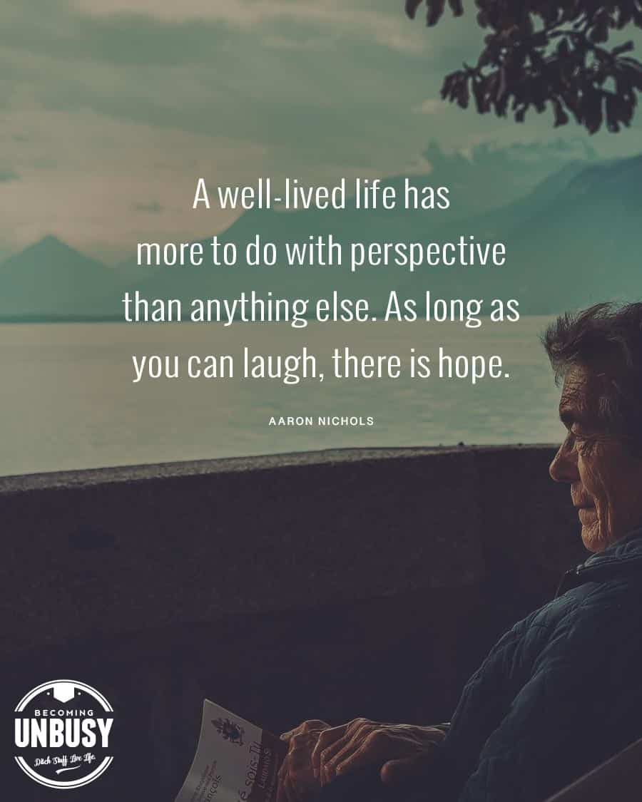 """An older gentleman looking out at a lake smiling, with the following quote over top, """"A well-lived life has more to do with perspective than anything else. As long as you can laugh, there is hope."""""""