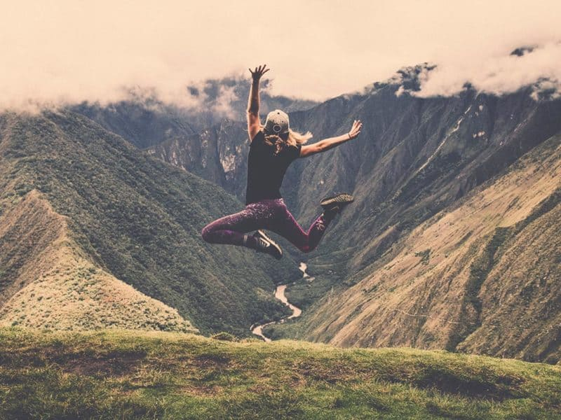 Photo of a woman jumping in the air with mountains in the distance.