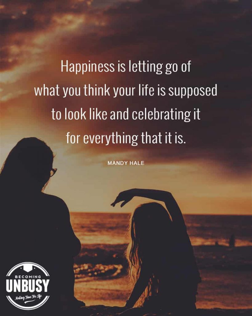 """A woman and girl sitting at a beach at dusk with a quote about change written over top reading, """"Happiness is letting go of what you think your life is supposed to look like and celebrating it for everything that it is."""""""