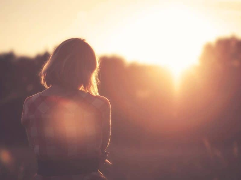 Woman in a field wearing a flannel crossing her arms watching the sun rise.