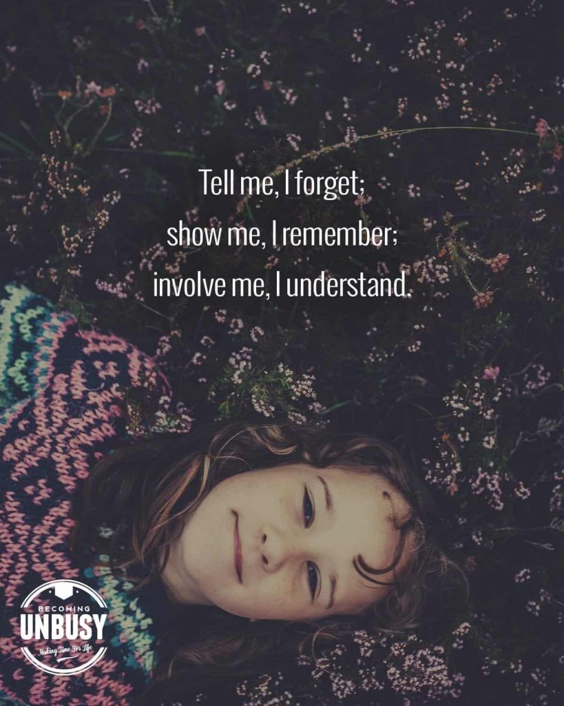 "A young girl laying face forward in a field of flowers with a quote written overtop reading, ""Tell me, I forget; show me, I remember; involve me, I understand."""