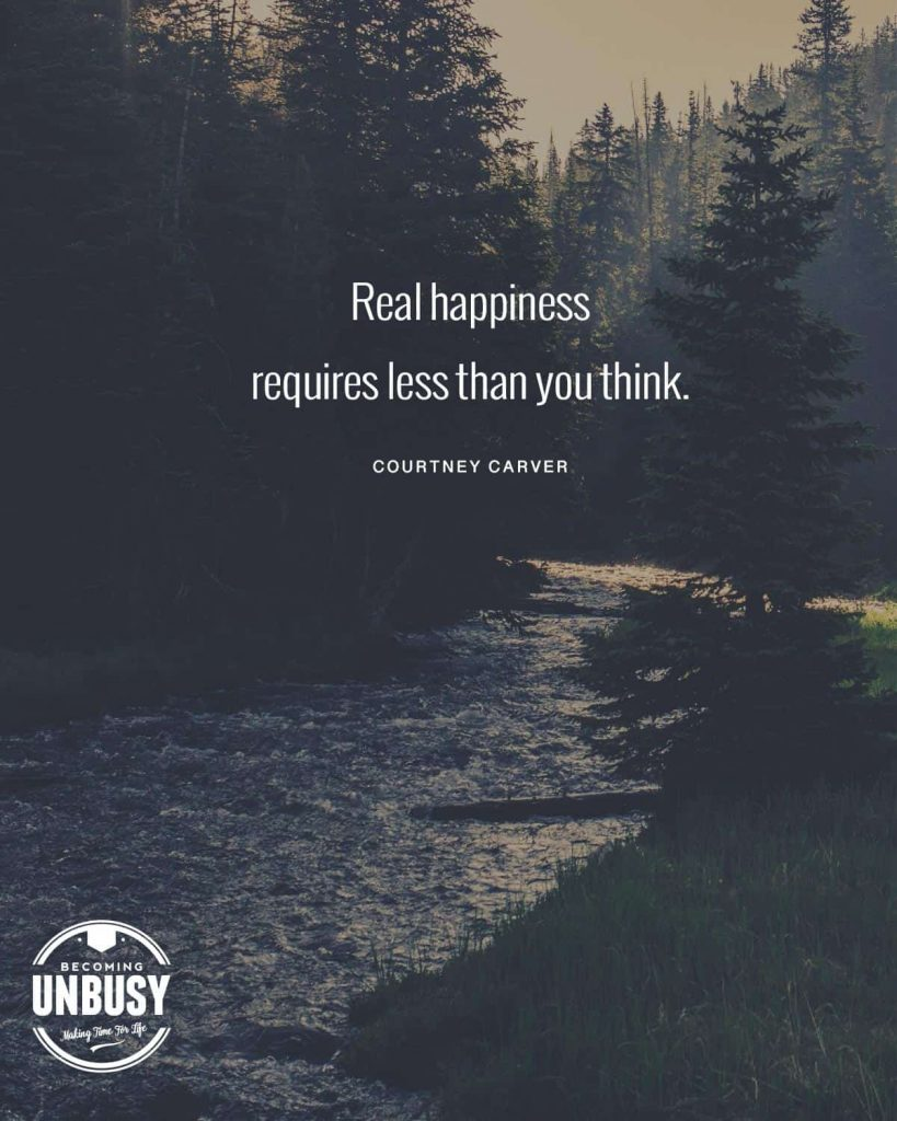"A river at dusk with pine trees surrounding it and a simple life quote written over top reading, ""Real happiness requires less than you think."""