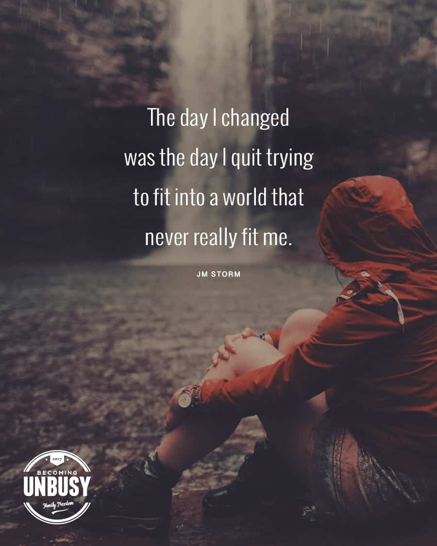 """Woman sitting near a waterfall in a raincoat, shorts, and hiking boots with her arms wrapped around her knees with the following JM Storm quote on top, """"The day I changed was the day I quit trying to fit into a world that never really fit me."""""""